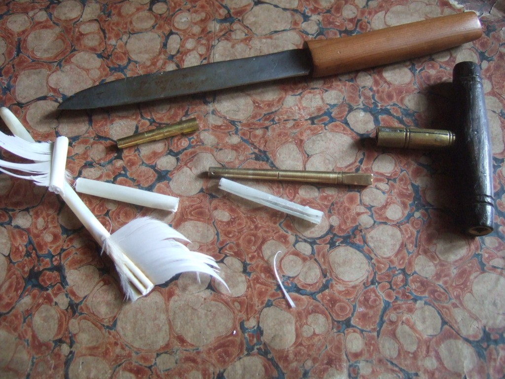 Goose quills to the left; the scraped seagull quill with the pin in the centre, the old brass sheet shim above.
